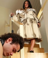 Beautiful mistress in luxurious fur coat humiliating her disobedient slave